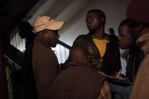 ***JOHANNESBURG, SOUTH AFRICA - JULY 24: A group of men take notes of who is and is not returning back to Zimbabwe to vote in the last week's election on the 31st of July at the Wednesday night service at the Central Methodist Church of South Africa, which 80% of people in attendances are Zimbabwean. Photo: Charlie Shoemaker